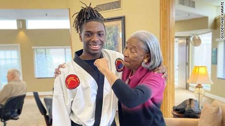 "In a photo taken pre-social distancing, Wall poses with a ""super nana"" at the local nursing home where he provided karate classes to senior citizens."