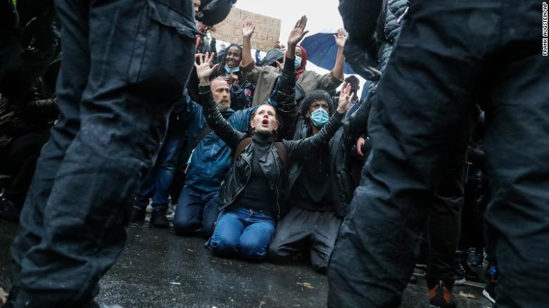 I manifestanti si inginocchiano di fronte agli agenti di polizia durante un'altra marcia di Black Lives Matter a Londra sabato.