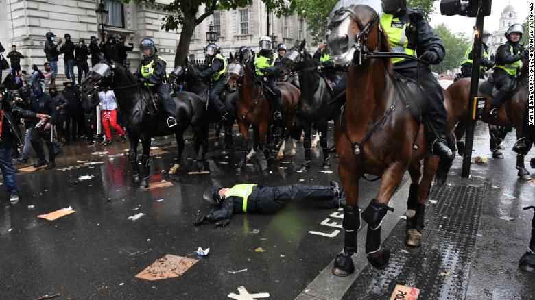 A mounted police officer lays on the road after her horse bolted.