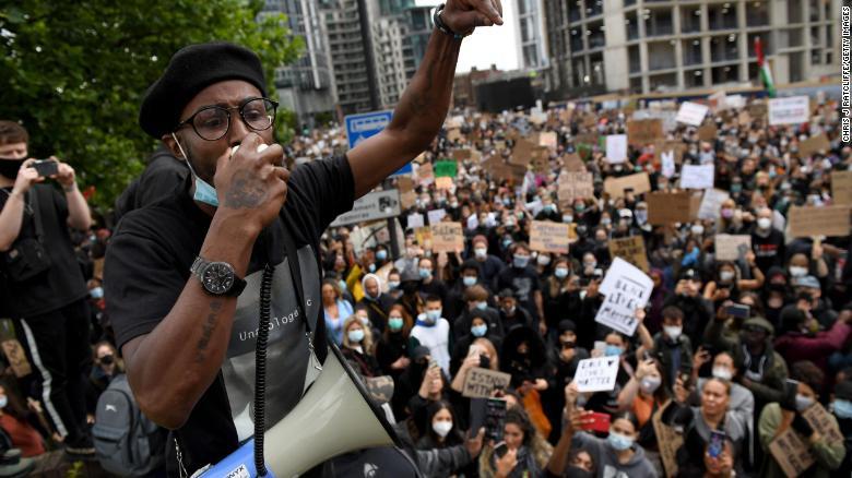 Un attivista si rivolge alla folla vicino all'ambasciata americana a Londra.
