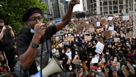 Bir eylemci Londra'daki ABD Büyükelçiliği yakınındaki kalabalığa hitap ediyor.