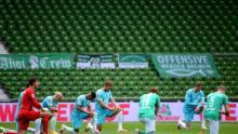 Jucătorii ambelor echipe se îngenuncheează pentru a protesta înaintea meciului din Bundesliga dintre SV Werder Bremen și VfL Wolfsburg din Germania, duminică.