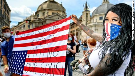 Protestocular Roma'da baş aşağı ABD bayrağı taşıyorlar.