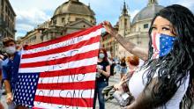 Protestatarii țin un steag american cu susul în jos la Roma.