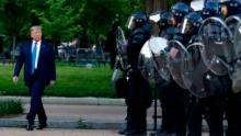 President Donald Trump walks past police in Lafayette Park after he visited St. John's Church across from the White House on Monday, June 1, 2020.