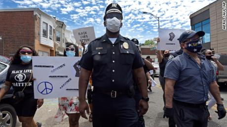 Lt. Zack James of the Camden County Metro Police Department marches along with demonstrators in Camden.