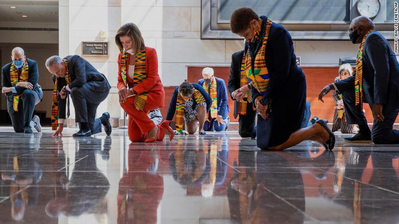 House Speaker Nancy Pelosi, center, and other members of Congress, kneel and observe a moment of silence at the Capitol's Emancipation Hall on Monday.