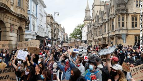 Protestors hold placards and shout slogans during during a protest called by the Rhodes Must Fall campaign calling for the removal of the statue of Cecil John Rhodes outside Oriel Cllege, at the University of Oxford on June 9, 2020.