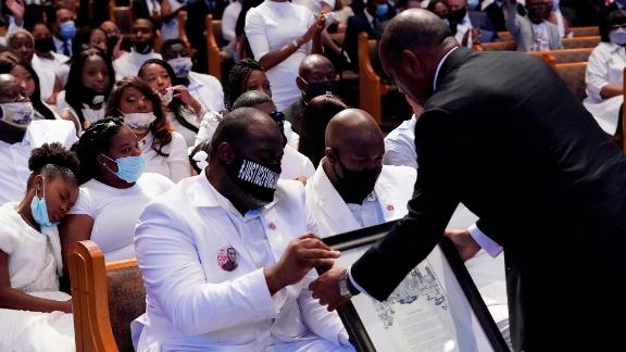 Houston Mayor Sylvester Turner hands the family a proclamation family and guests attend the funeral service for George Floyd at The Fountain of Praise church on June 9, 2020, in Houston. - George Floyd will be laid to rest Tuesday in his Houston hometown, the culmination of a long farewell to the 46-year-old African American whose death in custody ignited global protests against police brutality and racism.Thousands of well-wishers filed past Floyd's coffin in a public viewing a day earlier, as a court set bail at $1 million for the white officer charged with his murder last month in Minneapolis. (Photo by David J. Phillip / POOL / AFP) (Photo by DAVID J. PHILLIP/POOL/AFP via Getty Images)