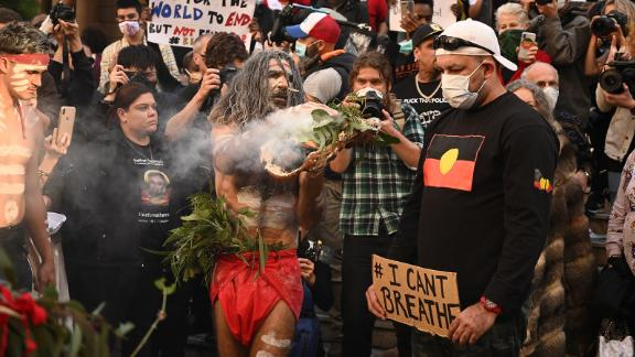 Aboriginal protesters perform a traditional smoking ceremony before the start of a Black Lives Matter demonstration to express solidarity with US protestors in Sydney on June 6, 2020.