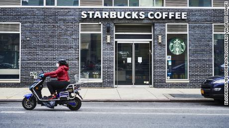 A person wearing a protective mask rides a scooter past a temporarily closed Starbucks coffeeshop in Brooklyn, NY, on April 27, 2020.
