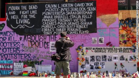 "A man takes photos of a makeshift memorial in the so-called ""Capitol Hill Autonomous Zone"" in Seattle."