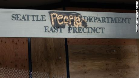 "A defaced sign for the East Precinct reads ""Seattle People Department"" on Wednesday in Seattle."