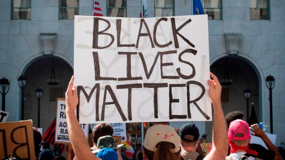 Supporters of Black Lives Matter, hold signs during a protest outside the Hall of Justice as they demonstrate against the death of George Floyd, in Los Angeles, California on June 10, 2020. (Photo by Mark RALSTON / AFP) (Photo by MARK RALSTON/AFP via Getty Images)