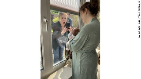 A woman meets her grandchild for the first time through a closed window during lockdown in Liverpool, England