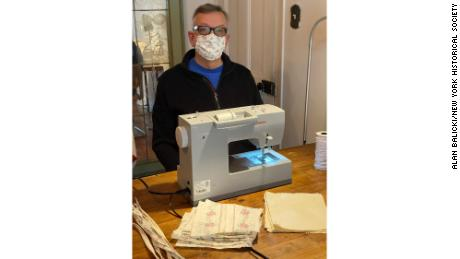 A man uses a sewing machine to create homemade face masks during lockdown in New York City