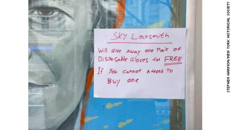 A sign appears in a locksmith's window offering a free pair of disposable gloves to anyone who can't afford it in New York City