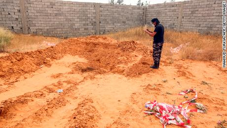 A member of security forces affiliated with the Libyan Government of National Accord (GNA)'s Interior Ministry takes a picture as he stands at the reported site of a mass grave in the town of Tarhuna, about 65 kilometres southeast of the capital Tripoli on June 11, 2020.