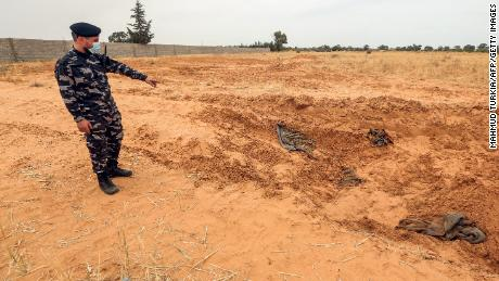 A member of security forces affiliated with the Libyan Government of National Accord (GNA)'s Interior Ministry points at the reported site of a mass grave in the town of Tarhuna, about 65 kilometres southeast of the capital Tripoli on June 11, 2020.