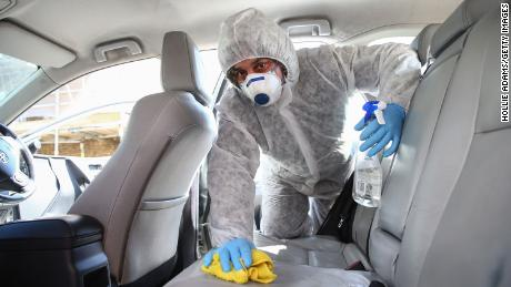 Uber driver Yasar Gorur wears personal protective equipment while cleaning his vehicle on April 14, 2020 in East London, United Kingdom.
