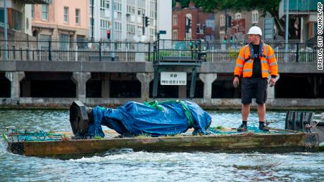 In this photograph made available by Bristol City Council, the statue of Edward Colston is recovered from the harbour in Bristol, Thursday June 11, 2020, after it was toppled by anti-racism protesters.