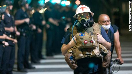 A protest medic walks near police as demonstrations continue over the killing of George Floyd despite the dangers of the widening coronavirus pandemic on June 6, 2020, in Los Angeles.