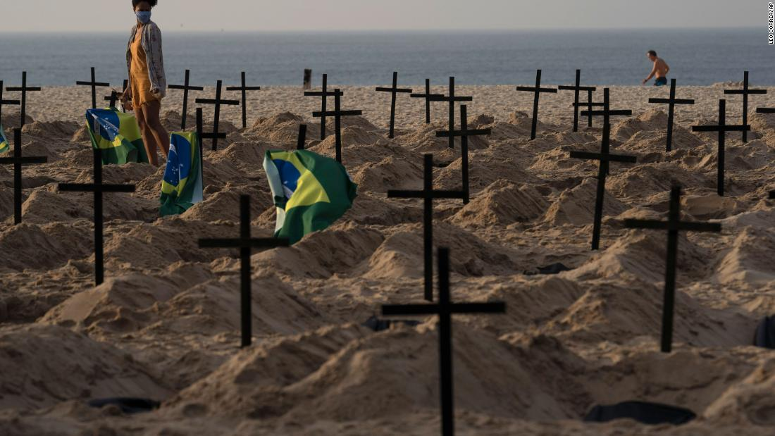 A woman walks amid symbolic graves on Copacabana beach, dug by activists from NGO Rio de Paz protesting the government's handling of the COVID-19 pandemic in Rio de Janeiro, Brazil, Thursday, June 11, 2020. A Brazilian Supreme Court justice ordered the government of President Jair Bolsonaro to resume publication of full COVID-19 data, including the cumulative death toll, following allegations the government was trying to hide the severity of the pandemic in Latin America's biggest country. (AP Photo/Leo Correa)