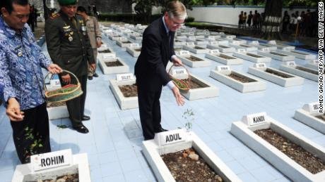 Former Dutch Ambassador to Indonesia Tjeerd de Zwaan, center, leaves flowers at the graves of victims of a 1947 massacre, in Rawagede, Indonesia, on December 9, 2011, when the Netherlands made a formal apology.