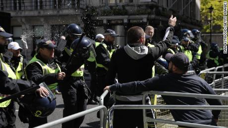 "A can of beer is thrown at police officers as activists from far-right linked groups clash with police on Parliament Street as far-right groups gathered to ""protect"" statues in London."