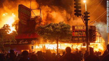 Protesters gather in front of a liquor store in flames near the Minneapolis Third Police Precinct, which was also gutted, in May during a protest over the death of George Floyd.