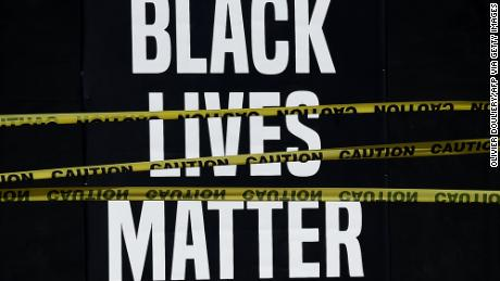 "A ""Black Lives Matter"" placard is seen behind caution tape during a peaceful protest in Washington against police brutality and the death of George Floyd."