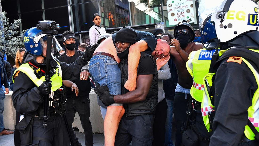 A protester carries an injured counter-protester to safety, near the Waterloo station during a Black Lives Matter protest following the death of George Floyd in Minneapolis police custody, in London, Britain, June 13, 2020. REUTERS/Dylan Martinez     TPX IMAGES OF THE DAY