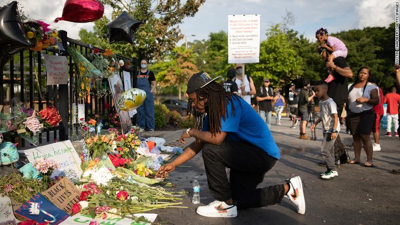 A man kneels at the memorial for Rayshard Brooks on June 14 in Atlanta.