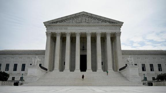 A woman walks down the steps of the US Supreme Court that released a decision that says federal law protects LGBTQ workers from discrimination on June 15, 2020 in Washington,DC.