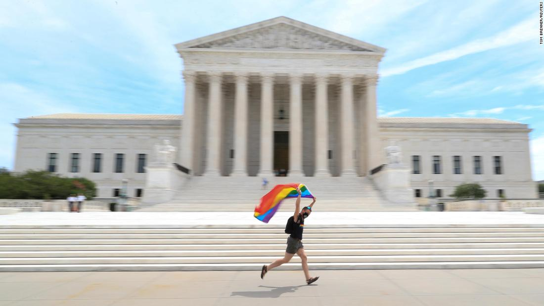 Joseph Fons holding a Pride Flag, runs in front of the U.S. Supreme Court building after the court ruled that a federal law banning workplace discrimination also covers sexual orientation, in Washington, June 15, 2020.