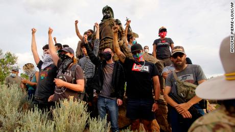 Demonstrators climb the statue of Juan de Oñate in Old Town in Albuquerque, New Mexico, while an armed member of the New Mexico Civil Guard stands by during a protest calling for its removal on Monday, June 15, 2020.
