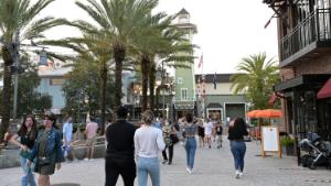 Visitors walk through the Disney Springs shopping, dining and entertainment complex, Tuesday, June 16, 2020, in Lake Buena Vista, Fla. Disney Springs reopened as part of a phased reopening during a new coronavirus pandemic, which included limited parking and entrances, temperature screenings prior to entry, face coverings required for guests ages 2 and up and social distancing. (Phelan M. Ebenhack via AP)