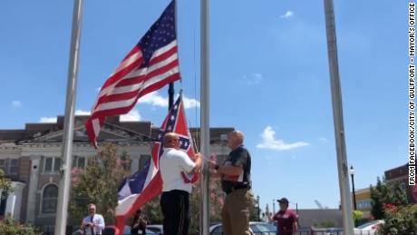 Officials in Gulfport, Mississippi, remove the state flag from the flagpole at City Hall.
