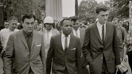 James Meredith walking to class in 1962 accompanied by US marshals and lawyer John Doar (right).