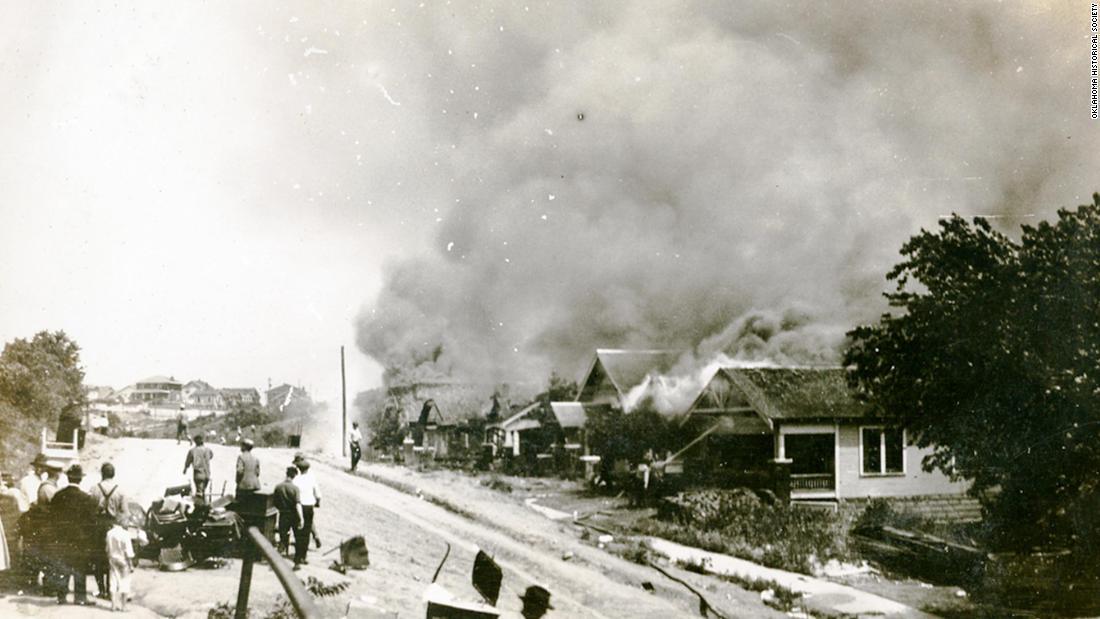 Un grup de oameni care privesc fum în depărtare provenind de la proprietăți deteriorate în urma masacrului de la Tulsa Race, Tulsa, Oklahoma, iunie 1921.