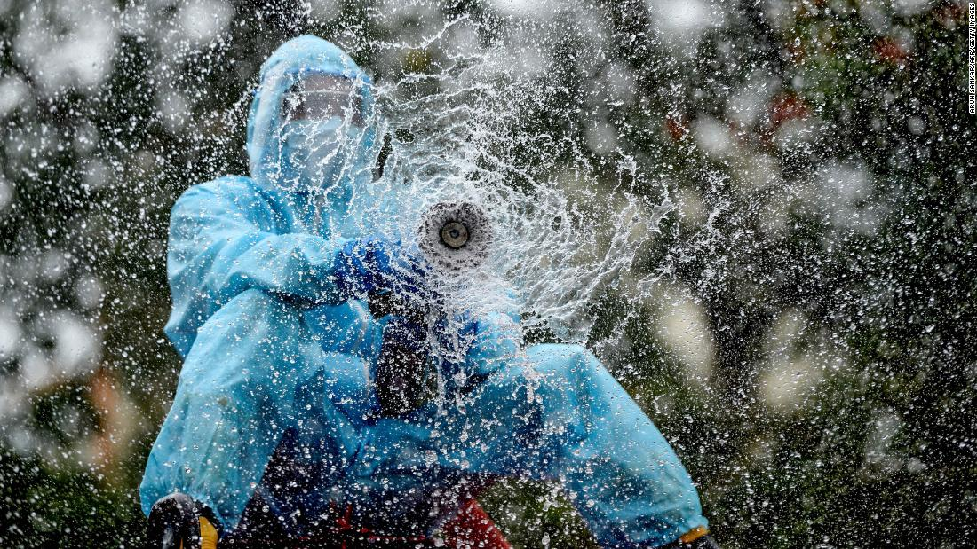 A firefighter in Chennai, India, sprays disinfectant to help prevent the spread of the coronavirus on June 11.