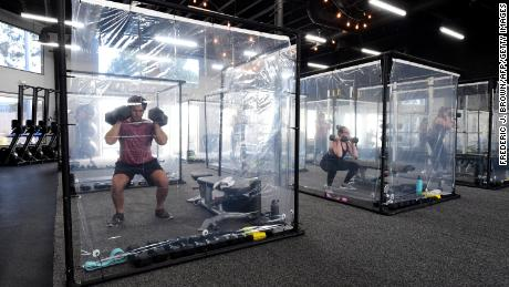 People exercise at Inspire South Bay Fitness behind plastic sheets in their workout pods on June 15 in Redondo Beach, California.