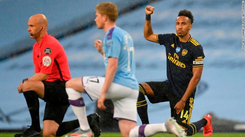 """皮埃尔·埃默里克·奥巴梅扬(Pierre-Emerick Aubameyang)在阿提哈德球场(Etihad Stadium)进行的曼彻斯特城和阿森纳之间的英超联赛比赛之前屈膝支持""""黑住病""""运动。"""
