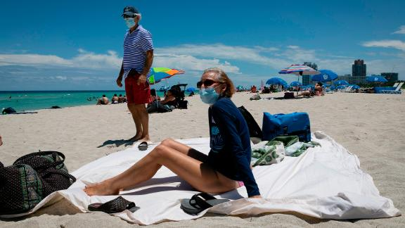 Diane, a nurse from Houston, sunbathes at the beach next to her husband, both wearing face coverings, in Miami Beach, Florida.