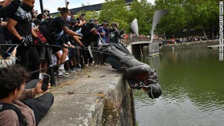 Protesters throw a statue of Edward Colston into a nearby river during a Black Lives Matter protest.