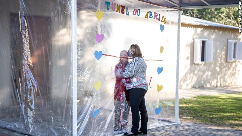 "A daughter and mother embrace through the thick plastic curtain and sleeves of the ""hug tunnel."""