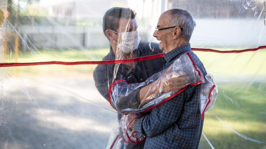 "A son hugs his father at  Três Figueiras via the ""hug tunnel,"" which staff developed to enable loved ones to embrace (Photo by Lucas Uebel/Getty Images)"