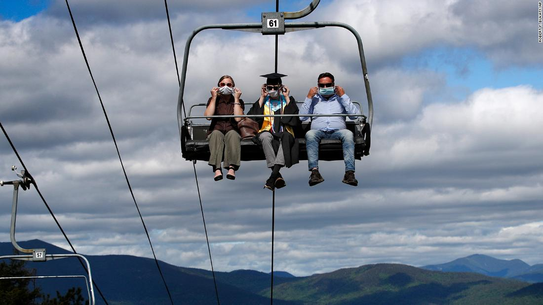 Kennett High School graduate Cole Bradley and his parents adjust their masks as they ride a chairlift to receive his diploma in North Conway, New Hampshire, on June 13. The school's unique commencement ceremony was created to adhere to social-distancing guidelines.