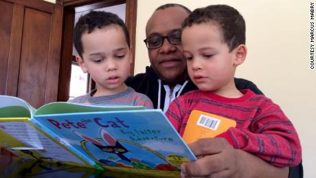 Mabry reads a book to his twin sons.