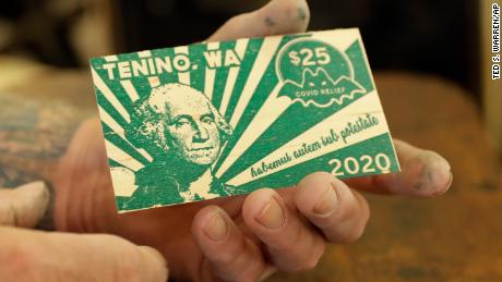 Loren Ackerman holds a piece of wooden money he printed on an 1890s-era press in Tenino, Washington.